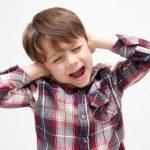 耳を抑える外国人の少年
