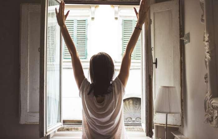 窓を開けて換気している女性