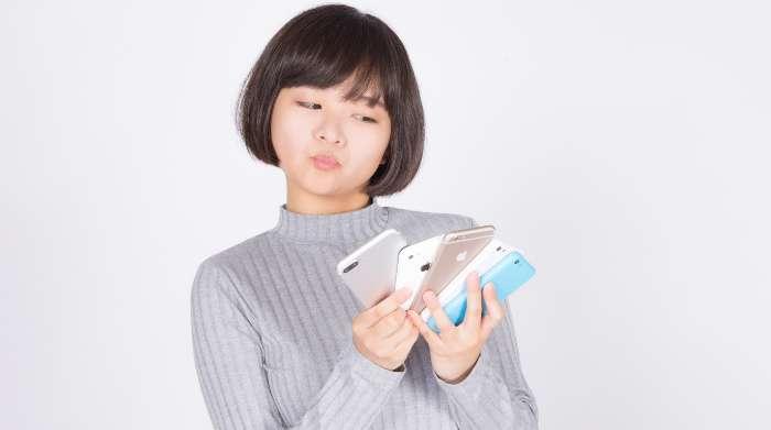 たくさんのスマートフォン(スマホ)を手に持つ女性