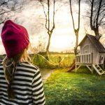 庭の小さな家を見る女の子