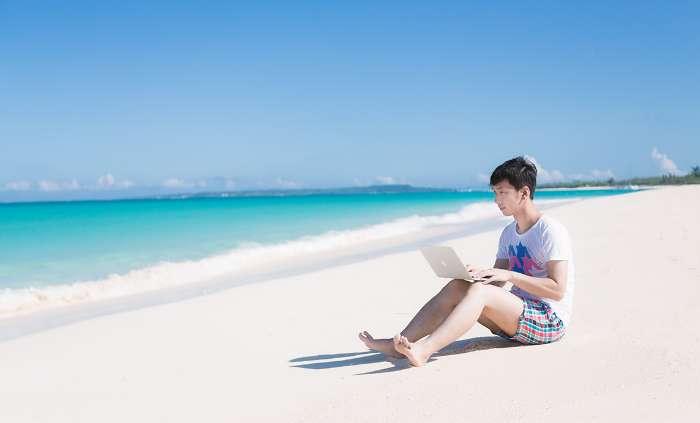 砂浜でレンタルモバイルルーター(ポケットWi-Fi)にパソコンを接続している男性