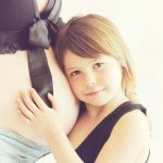 妊娠中の女性のお腹を抱える女の子