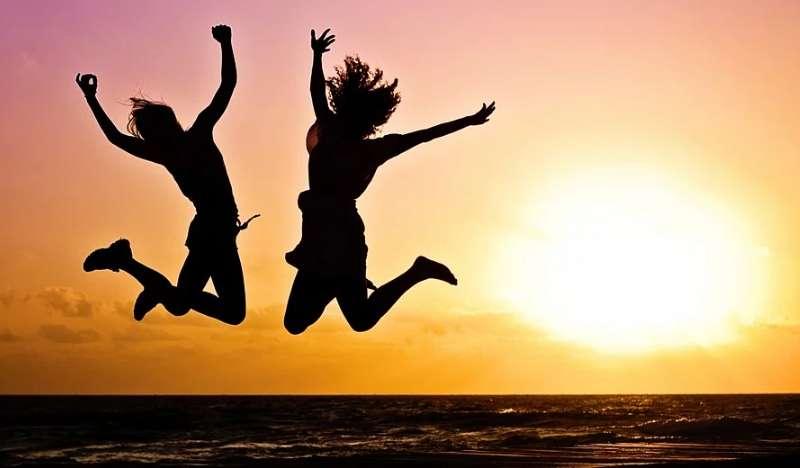 若者の男性と女性が夕日を見ながらジャンプする写真