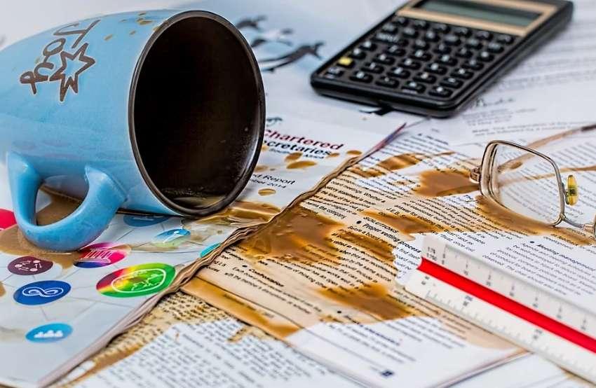 書類の上にコーヒーをこぼした写真