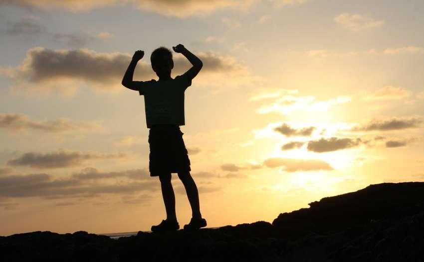 山の上で日に照らされながらガッツポーズする少年