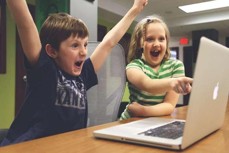 パソコンの画面を見て大喜びする男の子と女の子