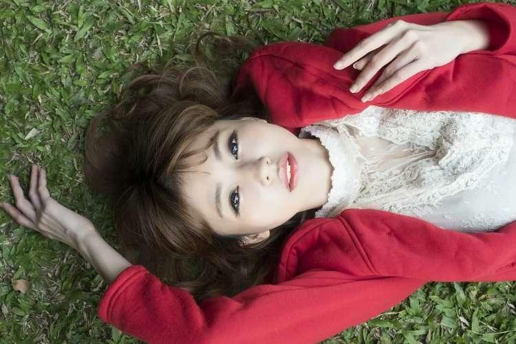 芝生に寝転がってこちらを見る女子大生