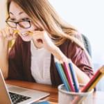 鉛筆を齧りながらパソコンの画面を見る女性