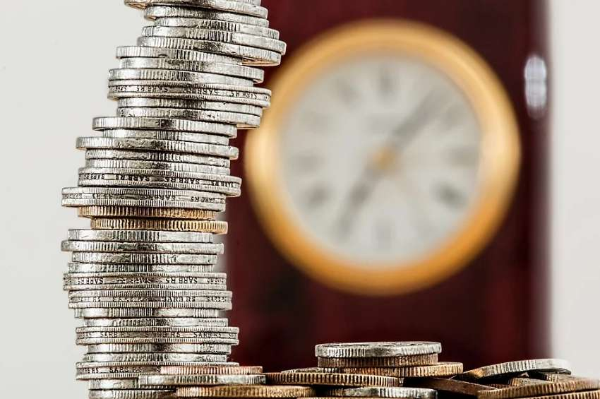 高く積まれたコインと時計