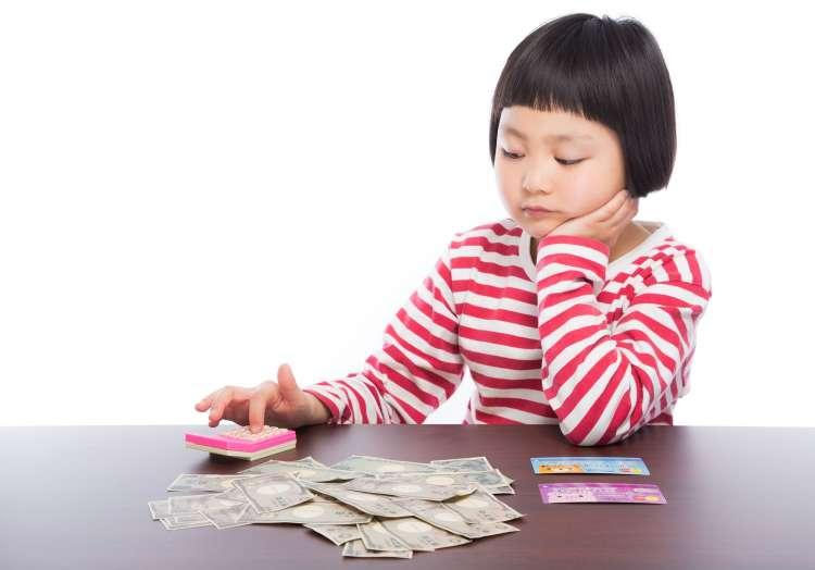 お金の計算をして悩む女の子