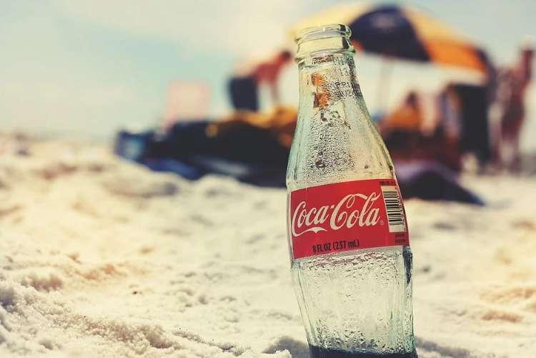 夏の砂浜に埋まっているコカ・コーラの瓶