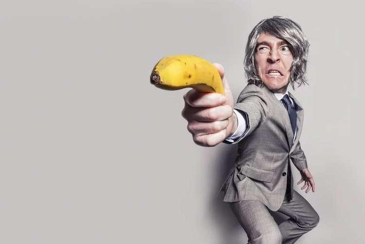 バナナを銃のように持って狙い定めるスーツ姿の男性