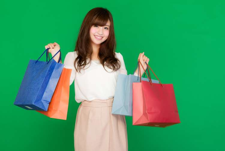 両手いっぱいの買い物袋を持ったセールが大好きな女性