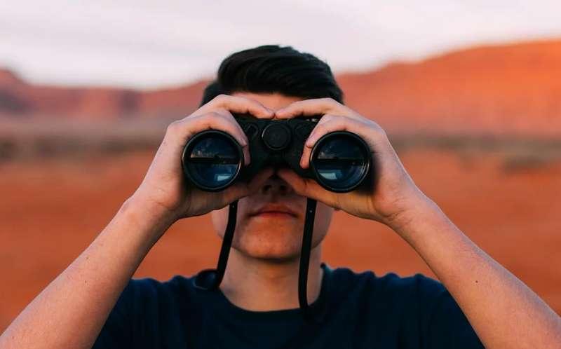 双眼鏡で遠くを見ている男性