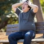 ベンチに座って頭を抱えて苦悩する太った男性