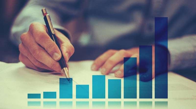 ペンで紙に字を書いている手元と棒グラフ