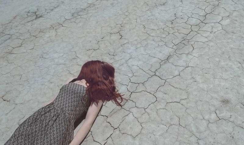 砂漠でうつ伏せになって倒れている女の子