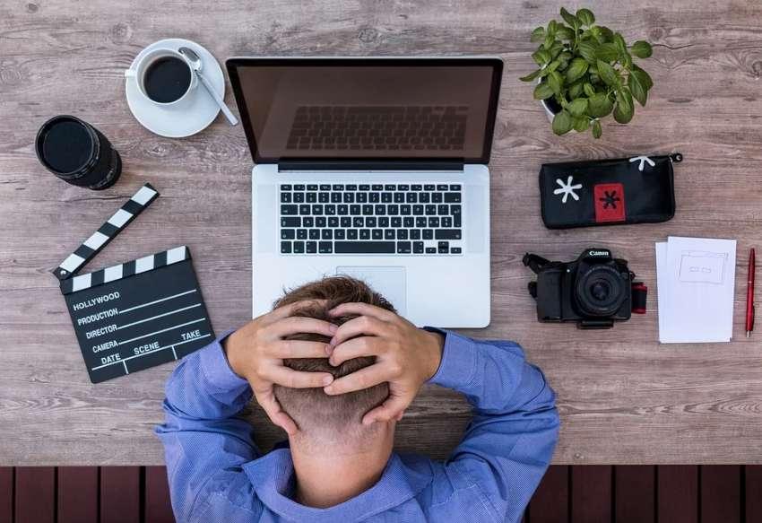 ノートパソコンの前で頭を抱える男