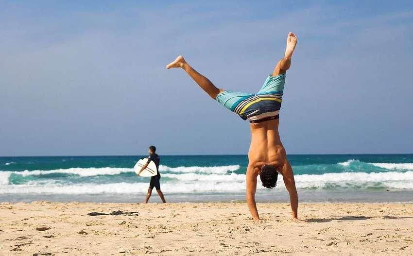 砂浜で逆立ちをする男