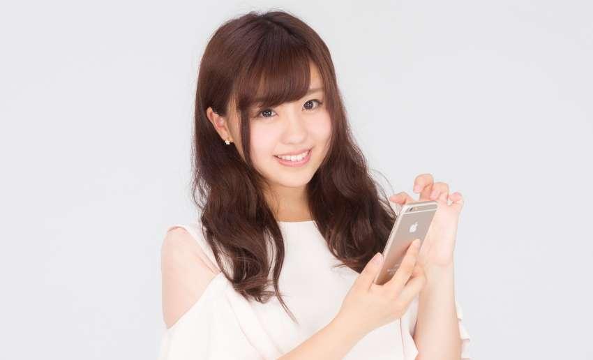 スマートフォンを手に持って微笑む女性