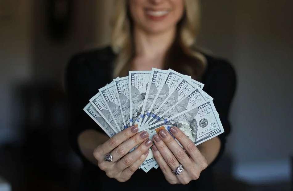 お札を手に持って見せつける女性