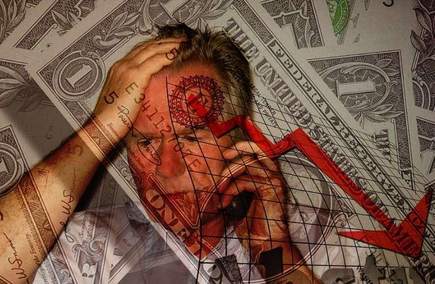 ドル紙幣の前で電話をしながら頭を抱えている暴落を悩む男性