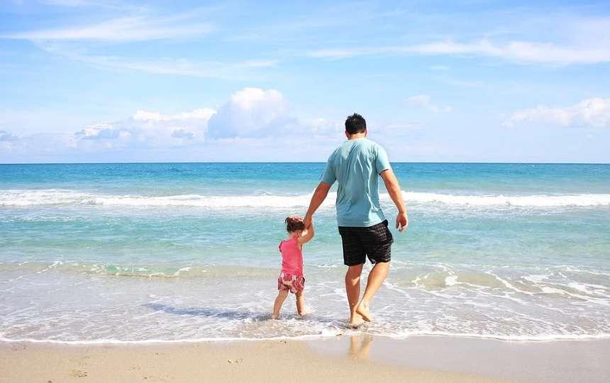 砂浜を歩く父親と娘