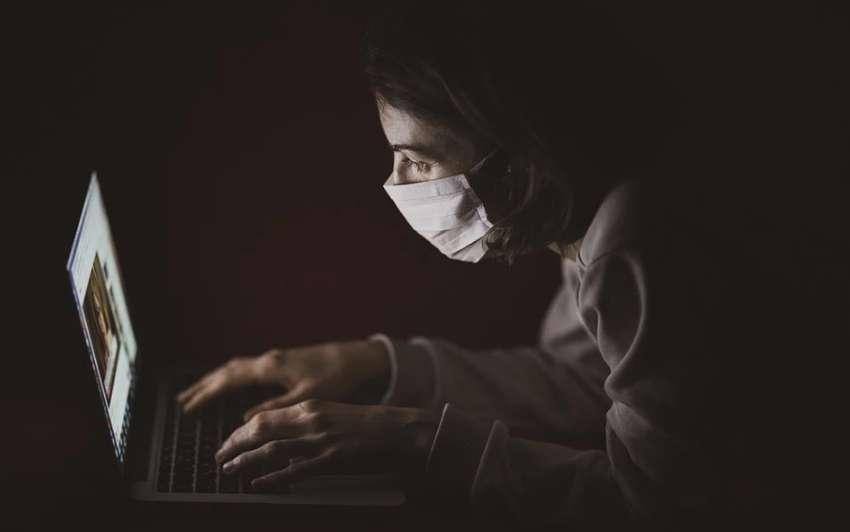 コロナショックでマスクを装着してパソコンを操作する人物