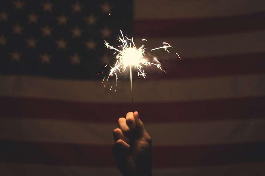 アメリカの国旗(星条旗)の前で花火を持つ手